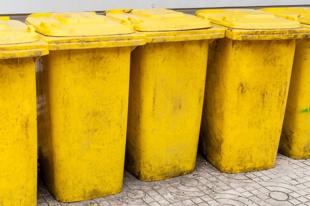 Dirty bin in a group made of yellow plastic