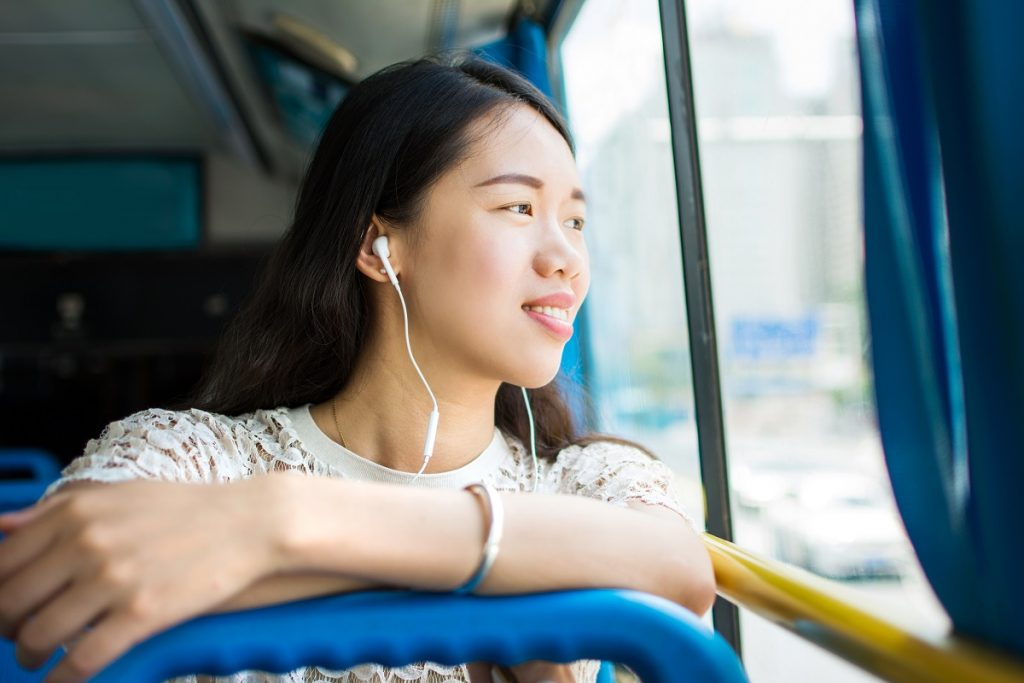 Girl listening to music on a public bus ride
